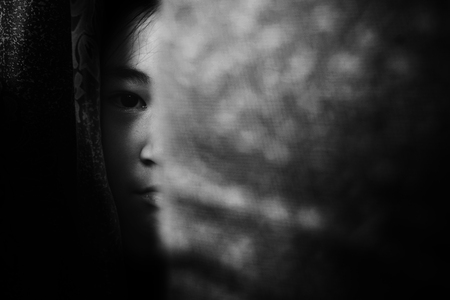 fear girl hiding behind curtain in white tone with shadow edge