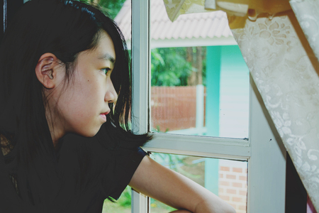 depress and hopeless girl with absent minded looking outside Stock Photo