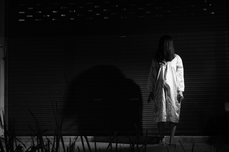 Mysterious Woman, Horror scene of scary ghost woman standing outdoor before metal door with light in white tone Banco de Imagens