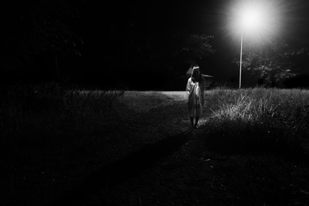 Mysterious Woman, Horror scene of scary ghost woman standing outdoor beside street with light in white tone Stock Photo