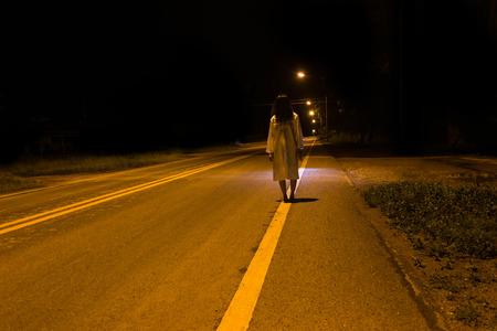 謎の女、屋外の光路上に立って怖い幽霊女の恐怖シーン 写真素材