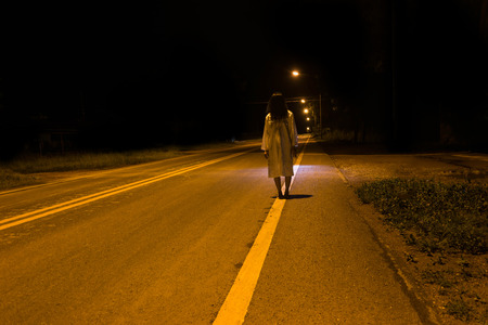 Mysterious Woman, Horror scene of scary ghost woman standing outdoor on street with light  Stock Photo