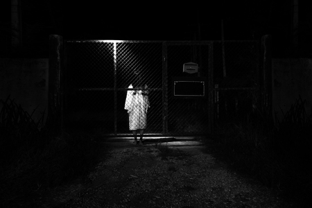 Mysterious Woman, Horror scene of scary ghost woman standing outdoor behind cage door with light in white tone
