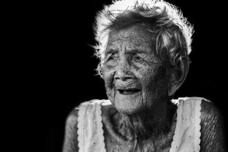 押し下げと無力な年配の女性の肖像, おばあちゃんは、屋外で座っているあなたの子供を待っている白いトーンで家に戻ってくる
