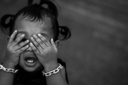 Foto des Kinderhandabdeckungsgesichtes mit mit dem Schreien, zurückhaltend, Kindesmissbrauch im weißen Ton mit Schattenrand