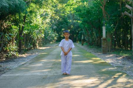 kind op witte kleding, oefen wandelen Meditatie in bos met vrede in min Stockfoto