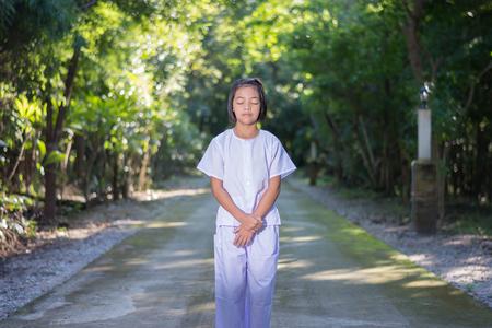 Kid op witte kleding, oefen waling meditatie in bos boom met vrede in gedachten