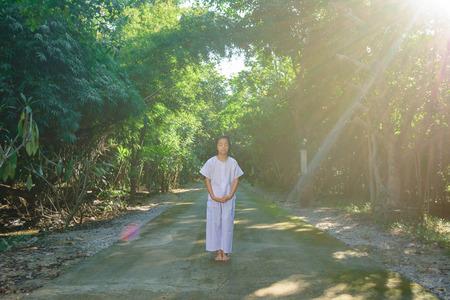 Kid sur des vêtements blancs , pratique de la pratique de la pratique dans l & # 39 ; arbre de la forêt avec la paix dans la porte Banque d'images - 90430935