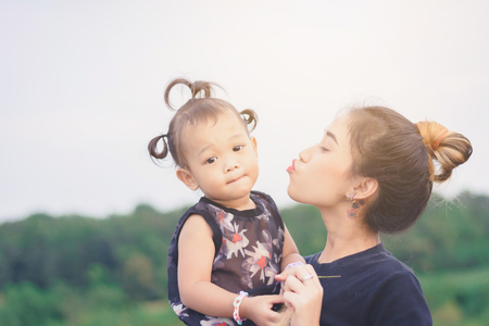 Young Asian mother with cute and sweet kid playing outdoor