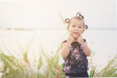 Portrait of Sweet and cute Asian kid with hair braid out door at countryside of Thailand