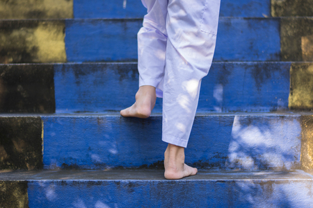 feet of kids without shoe, step on stair through the temple in forest