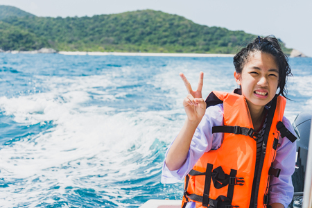 Sweet Asian girl feel exhausted sitting on speed boat after hours of snorkeling