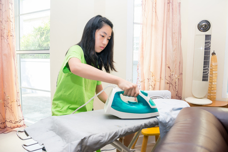 Sweet Asian girl ironing the cloth at home