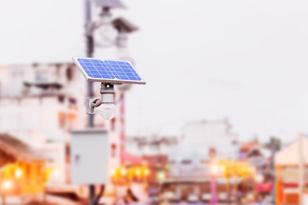light bulb with solar panel i n big town. concept clean energy in future Stok Fotoğraf