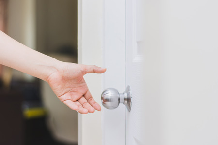 close up of woman's hand reaching to door knob, opening the door Stock fotó
