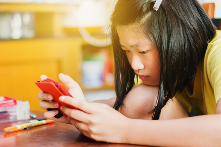 Sweet Asian Girl playing game in mobile phone at home
