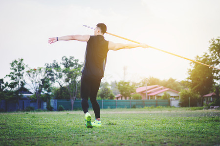 sportsman warming up and practicing javelin throw in yard Foto de archivo - 105804467
