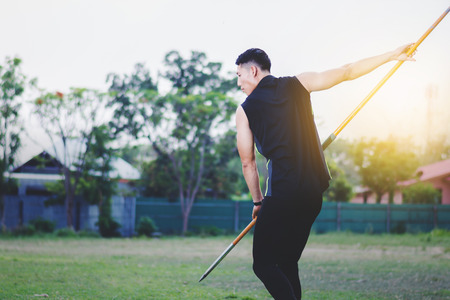 sportsman warming up and practicing javelin throw in yard Foto de archivo - 105804482