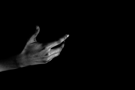 Hand of woman reaching out from the dark 스톡 콘텐츠