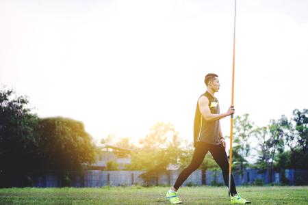 sportsman warming up and practicing javelin throw in yard Foto de archivo - 105804490