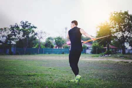 sportsman warming up and practicing javelin throw in yard Foto de archivo - 105804600