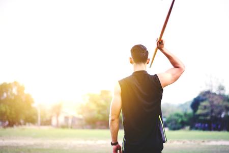 sportsman warming up and practicing javelin throw in yard Foto de archivo - 104769212