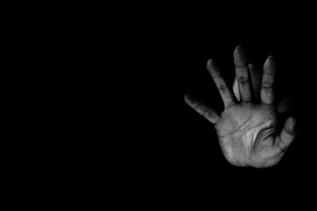Hand of woman reaching out from the dark Stockfoto
