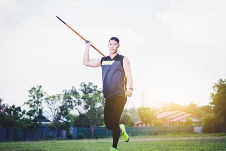 sportsman warming up and practicing javelin throw in yard Foto de archivo - 105804682