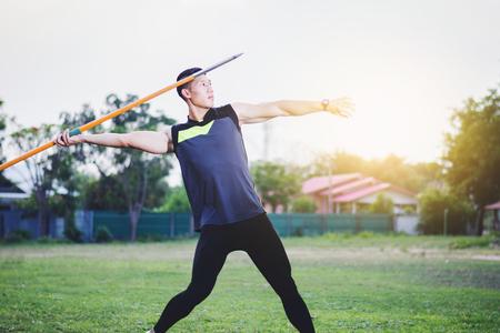 sportsman warming up and practicing javelin throw in yard Foto de archivo - 105911483