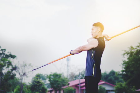 sportsman warming up and practicing javelin throw in yard Foto de archivo - 105911127