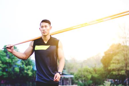sportsman warming up and practicing javelin throw in yard Foto de archivo - 105911133
