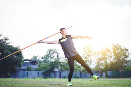 sportman warming-up en het beoefenen van speerwerpen in de tuin
