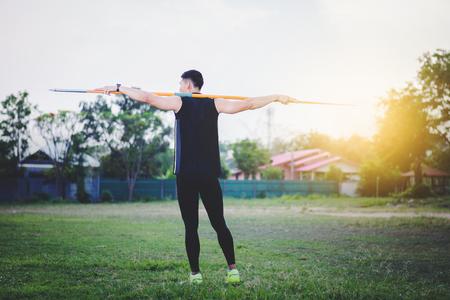 sportsman warming up and practicing javelin throw in yard Foto de archivo - 105804807