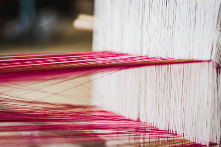 Close up of Thai Silk weaving on a traditional loom. Close up Thai silk thread. Making of thai silk. shallow depth of field Imagens