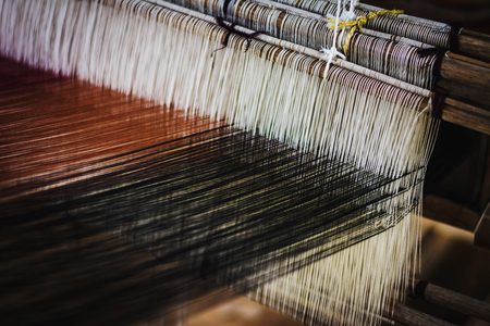 Close up of Thai Silk weaving on a traditional loom. Close up Thai silk thread. Making of thai silk. shallow depth of field Standard-Bild - 105908678