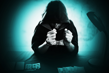 Boy in hood with handcuff at desk with money and Drug ,Crime and Drug concept