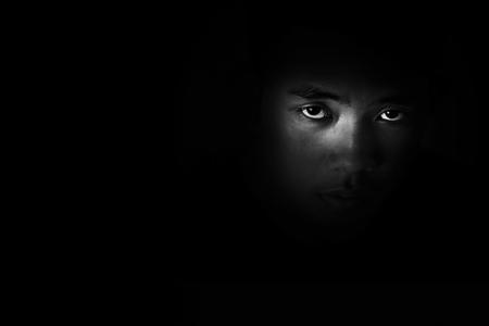 Ragazzo seduto in un angolo della stanza al buio con paura e senza speranza