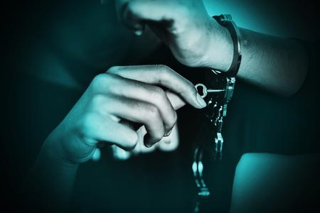 Boy unlocking handcuffs that bind him , escape from the arrest concept
