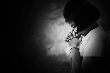 Depress and Hopeless girl praying in the dark in white tone Imagens