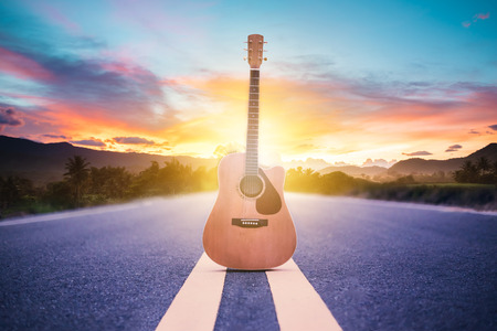 Wooden acoustic guitar lying on street with sunrise background, journey of musician concept