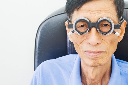Elderly man having hes eyes examined by an eye doctor on a testing tool in modern clinic, optometry concept Reklamní fotografie