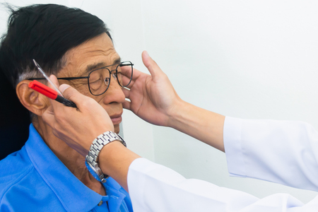 Optician male hands put glasses on elderly man testing his eye, ophthalmology concept.
