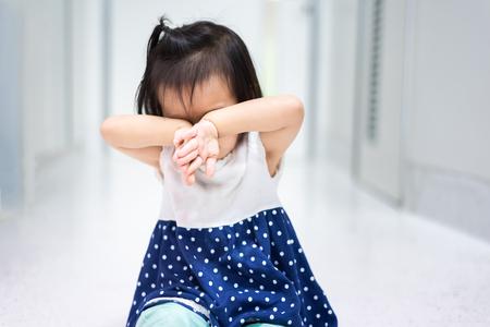 Petit bébé enfant assis sur le sol en train de pleurer et de se couvrir le visage avec sa main