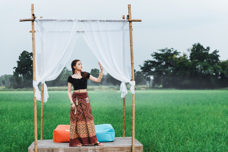 Beautiful Asian woman in local dress standing in small bamboo pavilion with cloth decoration and enjoy natural on bamboo bridge in rice field