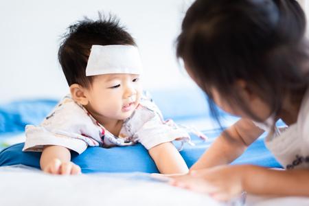 Unglückliches asiatisches kleines Babykind krank mit coolem Fieber-Jel-Pad auf der Stirn