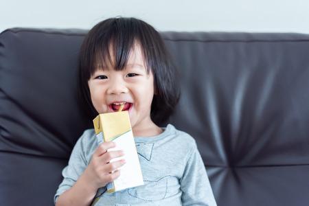 Glückliches süßes asiatisches Baby, das einen Karton Milch aus einer Kiste mit Strohhalm auf dem Sofa trinkt Standard-Bild