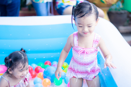 little children enjoy and have fun playing water in inflatable pool with colorful of small balls