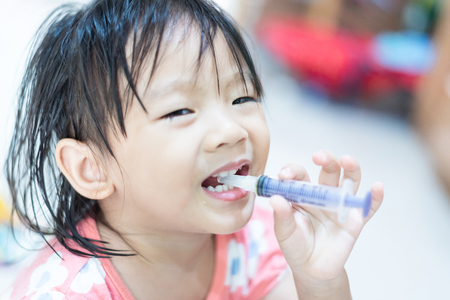 Little baby child feeding herself with water in syringe Banco de Imagens