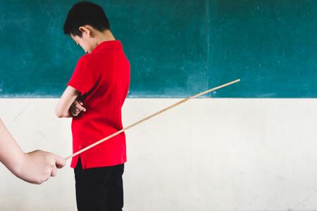 Étudiants physiquement punis par l'enseignant avec un petit bâton en bois