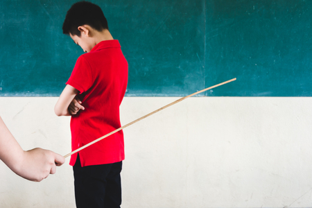 Students being physically punished by teacher with small wooden stick Stockfoto